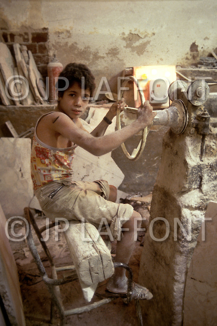 In Casablanca, Morocco, children are employed to cut hudge stones. Child labor as seen around the world between 1979 and 1980 - Photographer Jean Pierre Laffont, touched by the suffering of child workers, chronicled their plight in 12 countries over the course of one year.  Laffont was awarded The World Press Award and Madeline Ross Award among many others for his work.
