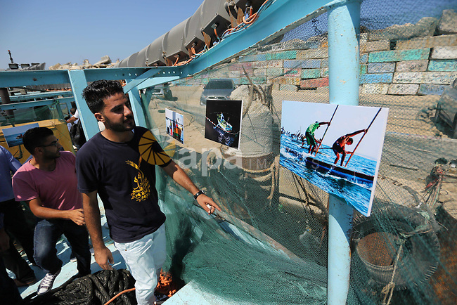 Palestinians attend a photo gallery on fishing boat, in Gaza seaport, on August 23, 2017. Photo by Ashraf Amra
