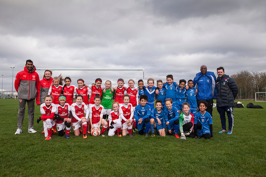 Both teams pose for a photo after the match. Arsenal Ladies Under 10 and AC Finchley boys team play a football game at Univeristy of Hertfordshire's campus sports village  football pitch in Hatfield.