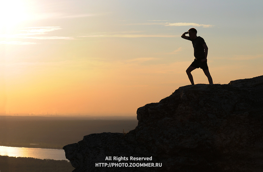 "Man observes Volga river from the highest point of Zhiguli mountains in Russian National Park ""Samara Luka""."
