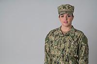 Woman in uniform studio portrait, model released,  DoD compliant for advertising, white background, framed for type
