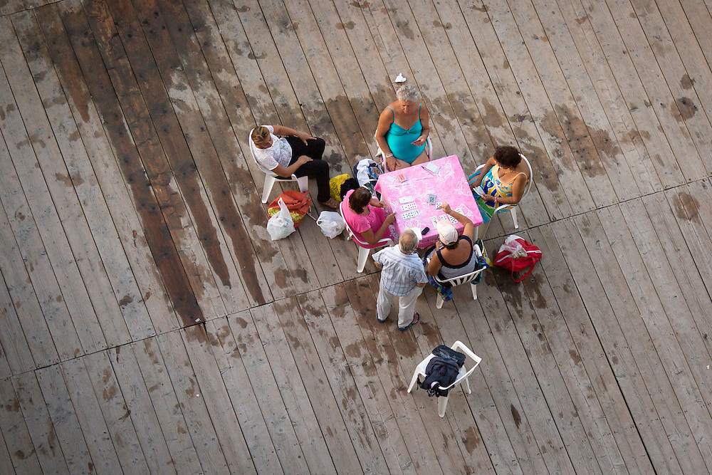 Locals play a game of cards on a deck overlooking the Gulf of Naples on Thursday, Sept. 17, 2015, in Sorrento, Italy. (Photo by James Brosher)