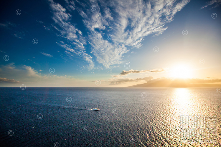 An aerial view of a boat heading towards Maui, with Lana'i and the setting sun in the distance.