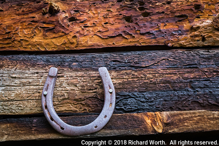 A horseshoe nailed above the door to a log building in the mountains, a common superstition for good luck.