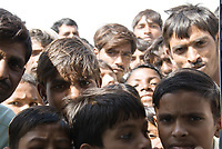 A group of Indian men and boys looking with great curiosity directly at the camera, India