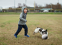 Lincoln Rowe, 4, and Fitzgerald chase a ball Friday, March 20, 2020, at Phillips Park in Bentonville. Check out nwaonline.com/200321Daily/ for today's photo gallery.<br /> (NWA Democrat-Gazette/Ben Goff)