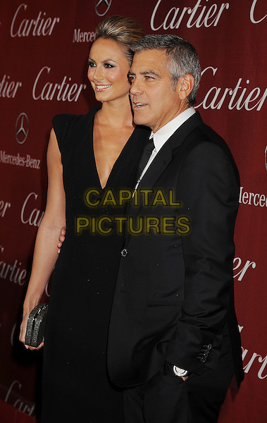 Stacy Keibler & George Clooney.The 2012 Palm Springs Film Festival Awards Gala at the Palm Springs Convention Center in Palm Springs, California, USA..January 7th, 2012.half length black dress suit side hand in pocket profile clutch bag tall short couple .CAP/ROT/TM.©Tony Michaels/Roth Stock/Capital Pictures
