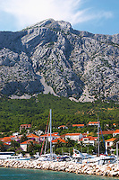 A view over the village and the massive mountains on the peninsula with undulating pattern. the pleasure boat harbour. Mount Sveti Ilija mountain. Orebic town, holiday resort on the south coast of the Peljesac peninsula. Orebic town. Peljesac peninsula. Dalmatian Coast, Croatia, Europe.