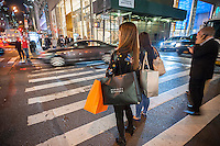 A woman waits at an intersection in New York holding shopping bags with her various purchases on Tuesday, October 4, 2016. (© Richard B. Levine)