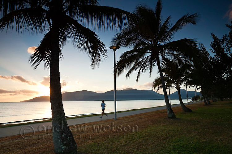 Jogger on the Esplanade at sunrise.  Cairns, Queensland, Australia