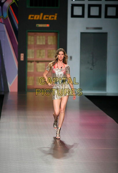 GISELE BUNDCHEN.At the Colcci Summer 2008 fashion show during Rio Fashion Week in Rio de Janeiro, Brazil..June 5th, 2007.full length catwalk runway gold sheer dress hand on hip silver belt strappy gladiator sandals shoes.CAP/PPG.©Photonews/People Picture/Capital Pictures *** Local Caption *** 00311061