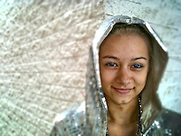 Teenage girl wearing silver sequined hoodie portrait with iPhone. Tiltshift