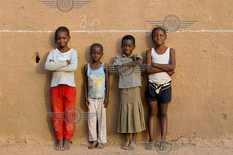 Estelle Bazie, Cedric Ouedraogo, Natacha Podo and Deborah Oceane Sanou, all eight years old, standing in front of a line that illustrates the global average height for children their age, in the informal settlement of Zongo. The area suffers from poor sanitation, which has an impact on health and nutrition, and can result in stunting.