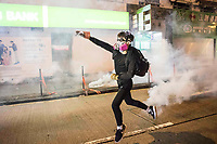 HONG KONG: 07 October 2019 A protester throws a tear gas canister back toward riot police during clashes in the Mong Kok region of Hong Kong this evening. Violence has continued throughout the city despite the introduction of a new law stating no masks can be warn which, in turn, has escalated the anger of the protesters.   <br /> Rick Findler / Story Picture Agency