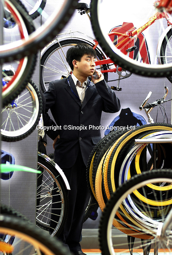A visitor makes a call surrounded by bicycles and accessories at the 14th China International Bicycle Fair in Shanghai, China. Despite the government's push to promote automobile ownership, the bicycle remains the most popular mode of transportation for China's masses. However gone are the ubiquitous and simple clunkers of the old days, more are looking into newer, lighter, and fancier models..14-APR-04