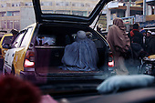 Kabul, Afghanistan<br /> November 2001<br /> <br /> A woman is loaded into the boot of a car like luggage at a local market.