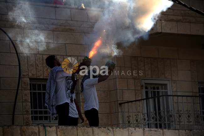 Palestinian protesters shot fireworks during a protest against the killing of Mohammed Aljaabis, who was killed by Israeli troops in Jerusalem on August 09, 2014. Israeli police have shot dead the driver of a bulldozer in Jerusalem after he rammed the vehicle into a passenger bus. An Israeli man was killd and and two others injured. Photo by Saeed Qaq