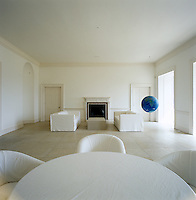 The garden room has a limestone floor and is furnished with sofas and chairs in white loose covers and an artwork by Pascale Petit