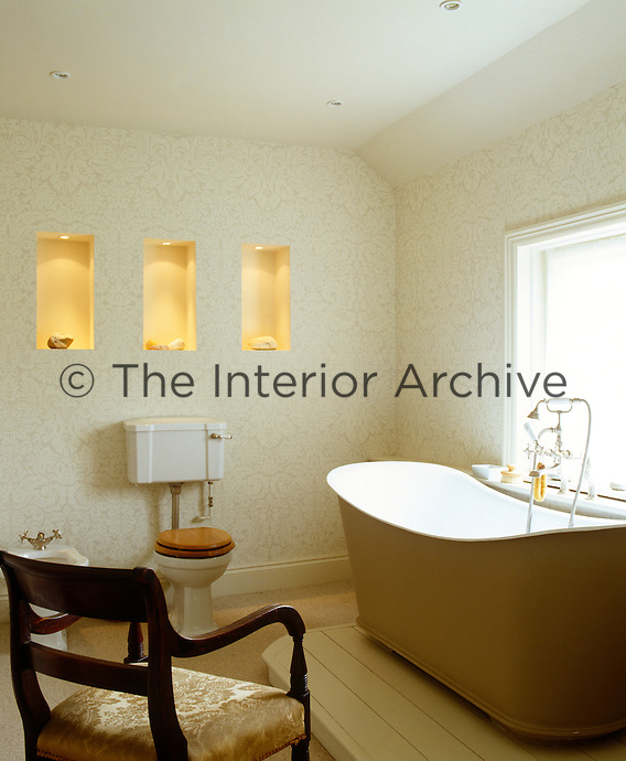 An antique free-standing bath on a raised wooden plinth in a contemporary bathroom