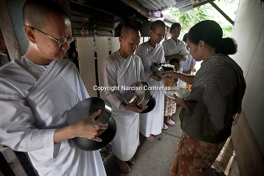 """A Buddhist woman offers charity and prayers to the Mae Chees clad in white robes as they stand silently in the early morning light, holding out their alms bowls hoping for food or monetary offerings. Vanished by centuries the lineage of """"Bhikkhu?nii"""" (Order of Nuns) has been brought to the ongoing Thai society's debate. White-clad thai nuns, who keep the eight precepts and have their heads and eyebrows shaved are known as the lon-existing """"mae chees"""" (low category to call the lay nuns). Females who have turned to religous life, as renunciants, live ostracized and marginalized by the Sangha (Buddhist community) and Thai society, denying them full access to the monastic life as well as rights and support from the government. Today nunhood is not recognized by any asian country belong to the Theravada Buddhist order. Most of the eight precept holders live in temples run by male abbots, at the shadow of the monks; with the exceptional existence of a few para-monastic institutions as the Sathira Dhammasathan meditation centre, where """"mae chees"""" are not allow to held a temple, but not denied to practice the spiritual life."""