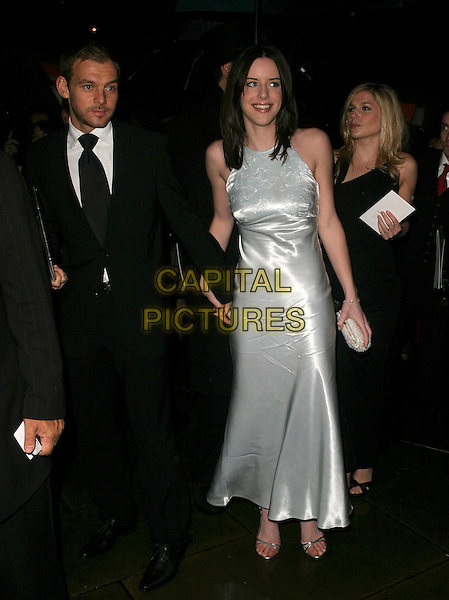 MICHELLE RYAN & GUEST.The Orange British Academy Film Awards aftershow & Grosvenor House Hotel, London, UK..February 19th, 2006.Ref: AH.full length black suit silver dress silk satin.www.capitalpictures.com.sales@capitalpictures.com.© Capital Pictures.