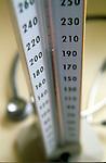 close-up of mercury rising on gauge on sphygmomanometer, stethoscope in background