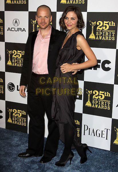 PETER SARSGAARD & MAGGIE GYLLENHAAL .25th Annual Film Independent Spirit Awards held At The Nokia LA Live, Los Angeles, California, USA,.March 5th, 2010 ..arrivals Indie Spirit Full length married couple husband wife pink peach shirt black suit one shoulder grey gray dress hand on hip tights shoes arm around  .CAP/ADM/KB.©Kevan Brooks/Admedia/Capital Pictures