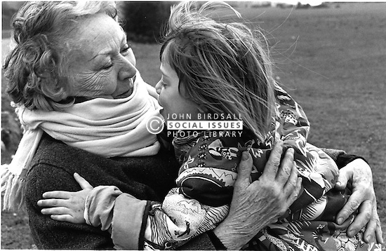 Elderly woman hugging young girl,