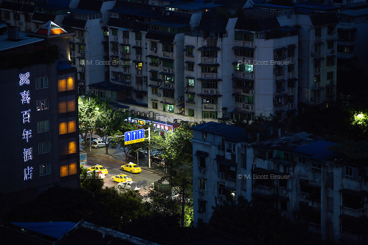 Taxis travel along a road between apartment buildings in the Jiangbei District of Chongqing, China.