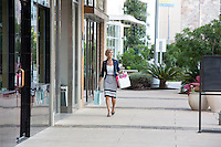 Attractive female shopper walks down the sidewalk at an outdoor shopping mall in Austin, Texas