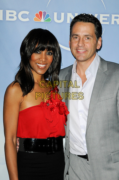 SHAUN ROBINSON & TONY POTTS.The NBC Universal Press Tour Cocktail party at the Langham Huntington Hotel in Pasadena, California, USA..January 10th, 2010.half length top dress black waist belt high waisted red one shoulder rosettes flowers corsages grey gray suit .CAP/ROT.©Lee Roth/Capital Pictures