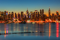 The Manhattan skyline during morning twilight as viewed over the Hudson River looking east from New Jersey.  The cool blue eastern sky was accented with tinges of orange that began to show in the hour before sunrise.