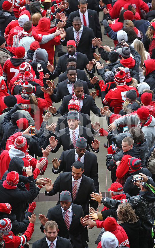 The Ohio State University football team high fives fans as they make their way from St John Arena to the Ohio Stadium on November 1, 2014. (Chris Russell/Dispatch Photo)