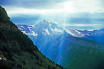 sunlight beams over Mt Cannon mountain into a valley in Glacier National Park Montana USA