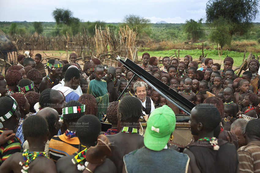 "Ethiopia. Southern Nations, Nationalities, and Peoples' Region. Omo Valley. Turmi. Hamar tribe (also spelled Hamer). Pastoralist group. Marc Vella is a french musician and a nomadic pianist. Over the last 25 years he has travelled with his Grand Piano in around forty countries to celebrate humanity. Creator of ""La Caravane amoureuse"" (The Caravan of Love) he takes people with him to say ""I love you"" to others and ""lovingly conquered"" their hearts and souls. The Omo Valley, situated in Africa's Great Rift Valley, is home to an estimated 200,000 indigenous peoples who have lived there for millennia. Amongst them are 60'000 to 70'000 Hamar, an Omotic community inhabiting southwestern Ethiopia. Southern Nations, Nationalities, and Peoples' Region (often abbreviated as SNNPR) is one of the nine ethnic divisions of Ethiopia. 7.11.15 © 2015 Didier Ruef"