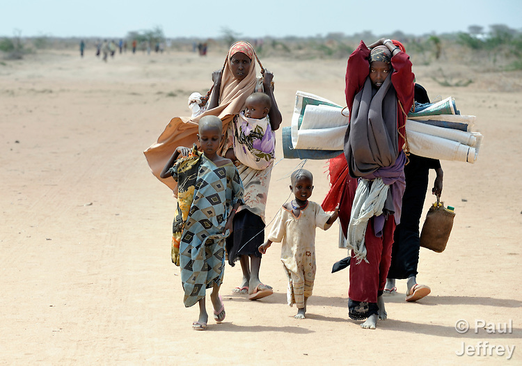 Habiba Ibrahim Ali (right), 20, a Somali woman who arrived in recent weeks at the Dadaab camp in northeastern Kenya, walks with another woman and their children to a new extension of the world's largest refugee settlement. Swelled with tens of thousands of recent arrivals fleeing drought in Somalia, the camp has been unable to absorb the newest arrivals. The Lutheran World Federation, a member of the ACT Alliance, is manager of the camp and in July began moving hundreds of families into tents in the extension.