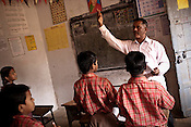 Students and teacher collaborate in singing Aflatoon songs as they attend their classes in a government run school in Caregaon, Thane, Maharashtra. These schools run a specially designed concept of 'aflatoon' as part of the curriculam whereby students are made aware of their child as described in the convention of rights of child. These students are made aware of right to survival, right to protection, right to development and right to participation.
