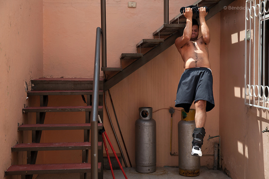 "Rodrigo Fernandez Loya, a player from Guerreros Aztecas, does pull-ups on a stairwell in his backyard in Mexico City, Mexico on September 25, 2014. Rodrigo, 25, lost his left leg in 2012 when he saved a girl from an onrushing train. Involved in a local 'barrio' gang until his accident, he says that the self-discipline he has developed during his time with Guerreros Aztecas has helped him turn his life around and he is currently studying for his high school diploma. Rodrigo has made the shortlist and is one of the team's biggest hopes to represent Mexico at this December's Amputee Soccer World Cup in Sinaloa. Guerreros Aztecas (""Aztec Warriors"") is Mexico City's first amputee football team. Founded in July 2013 by five volunteers, they now have 23 players, seven of them have made the national team's shortlist to represent Mexico at this year's Amputee Soccer World Cup in Sinaloa this December. The team trains twice a week for weekend games with other teams. No prostheses are used, so field players missing a lower extremity can only play using crutches. Those missing an upper extremity play as goalkeepers. The teams play six per side with unlimited substitutions. Each half lasts 25 minutes. The causes of the amputations range from accidents to medical interventions – none of which have stopped the Guerreros Aztecas from continuing to play. The players' age, backgrounds and professions cover the full sweep of Mexican society, and they are united by the will to keep their heads held high in a country where discrimination against the disabled remains widespread. (Photo by Bénédicte Desrus)"
