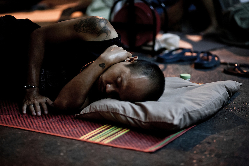 A Red Shirt militant is sleeping on the ground near the barricade of Silom in the camp of Bangkok. Every night Red Shirts were waiting for an assautl after the failure of negociations and relayed themselves to guard the camp. The assault came thre weeks later.