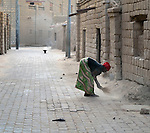 A woman sweeps the street in front of a house early in the morning in Timbuktu, the northern Mali city that was seized by Islamist fighters in 2012 and then liberated by French and Malian soldiers in early 2013. During the jihadis' rule, girls and women could not appear in public unless they were completely covered.