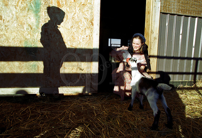 Mamie Ludwig bottle feeds a 2 week old goat, on January 31, 2000, as her brother looks on.. John Ulan/Epic Photography Inc..