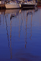 A pair of sailboats are reflected in the waters of the marina at Cornucopia, Wisconsin.