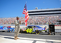 Sept. 21, 2008; Dover, DE, USA; A soldier holds an American flag next to the car of Nascar Sprint Cup Series driver Jimmie Johnson prior to the Camping World RV 400 at Dover International Speedway. Mandatory Credit: Mark J. Rebilas-