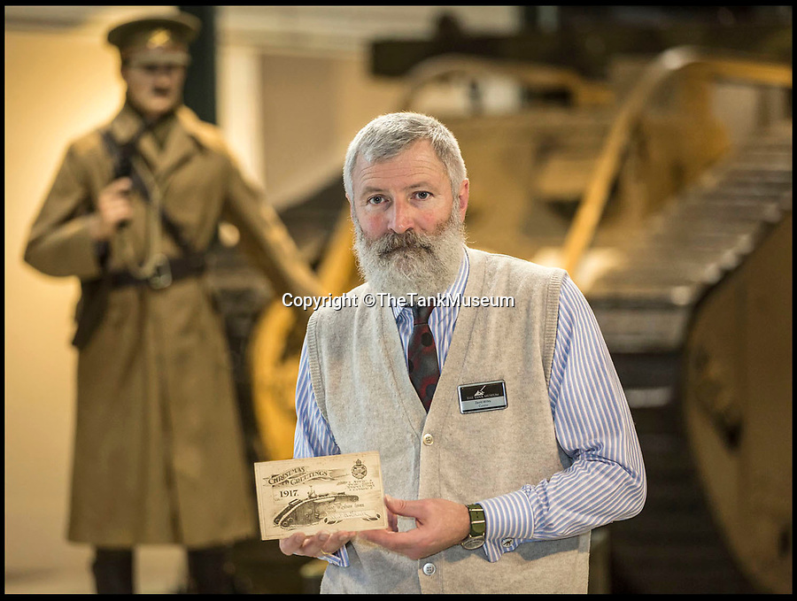 BNPS.co.uk (01202 558833)<br /> Pic: TheTankMuseum/BNPS<br /> <br /> Tank Museum curator David Willey with a rediscovered Christmas card sent by tank hero Capt Elliot Hotblack 100 years ago. <br /> <br /> A Christmas card sent by one of the First World War's most heroic tank officers has been unearthed 100 years later.<br /> <br /> Elliot Hotblack posted the simple card from 'Advance Headquarters Tank Corps' in December 1917, presumably to his parents in Norfolk.<br /> <br /> It includes a print of a crewman waving his cap from a Mark IV tank beneath the words 'Christmas Greetings.<br /> <br /> The card has been found in the archives of the Tank Museum in Dorset where it will now go on display.