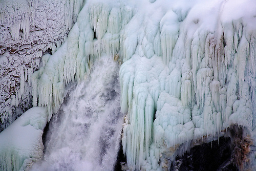 ICE FORMS ALONG SIDE THE WATER FROM THE LOWER FALLS OF THE YELLOWSTONE RIVER AT YELLOWSTONE NATIONAL PARK