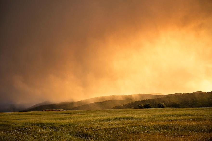 Virga clouds are illuminated by the setting sun in the Beaverhead Mountains near Wisdom, Montana.