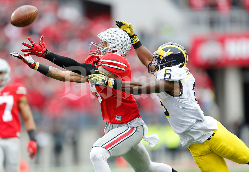 Ohio State Buckeyes wide receiver Devin Smith (9) catches a 50-yard pass from Ohio State Buckeyes quarterback J.T. Barrett (16) under pressure from Michigan Wolverines defensive back Raymon Taylor (6) in the third quarter the college football game between the Ohio State Buckeyes and the Michigan Wolverines at Ohio Stadium in Columbus, Saturday morning, November 29, 2014. The Ohio State Buckeyes defeated the Michigan Wolverines 42 - 28. (The Columbus Dispatch / Eamon Queeney)