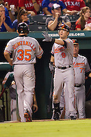 Baltimore Orioles outfielder Nate McClouth #9 celebrates with teammate Omar Quintanilla#35  after he scored during the Major League Baseball game against the Texas Rangers on August 21st, 2012 at the Rangers Ballpark in Arlington, Texas. The Orioles defeated the Rangers 5-3. (Andrew Woolley/Four Seam Images).