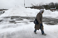 Matt Jones walks past a large pile of snow built up by plows in the Barracks Road Shopping Center Thursday after a snowfall in Charlottesville, VA. Photo/Andrew Shurtleff