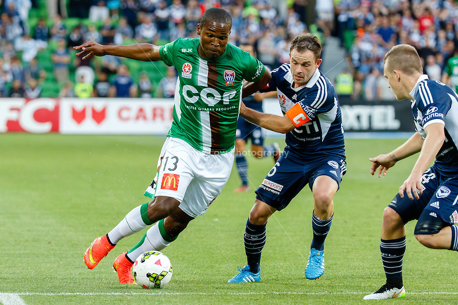 Edson MONTANO (13) of the Jets and Leigh BROXHAM of the Victory fight for the ball in round 12 A-League match between Melbourne Victory and Newcastle Jets at AAMI Park in Melbourne, Australia during the 2014/2015 Australian A-League season. Melbourne def Newcastle 1-0